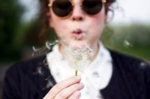 Woman blowing a dandelion flower