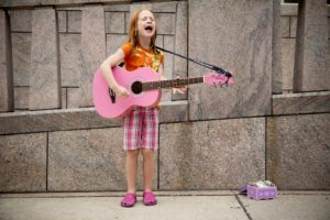 Red-haired girl plays guitar and sings