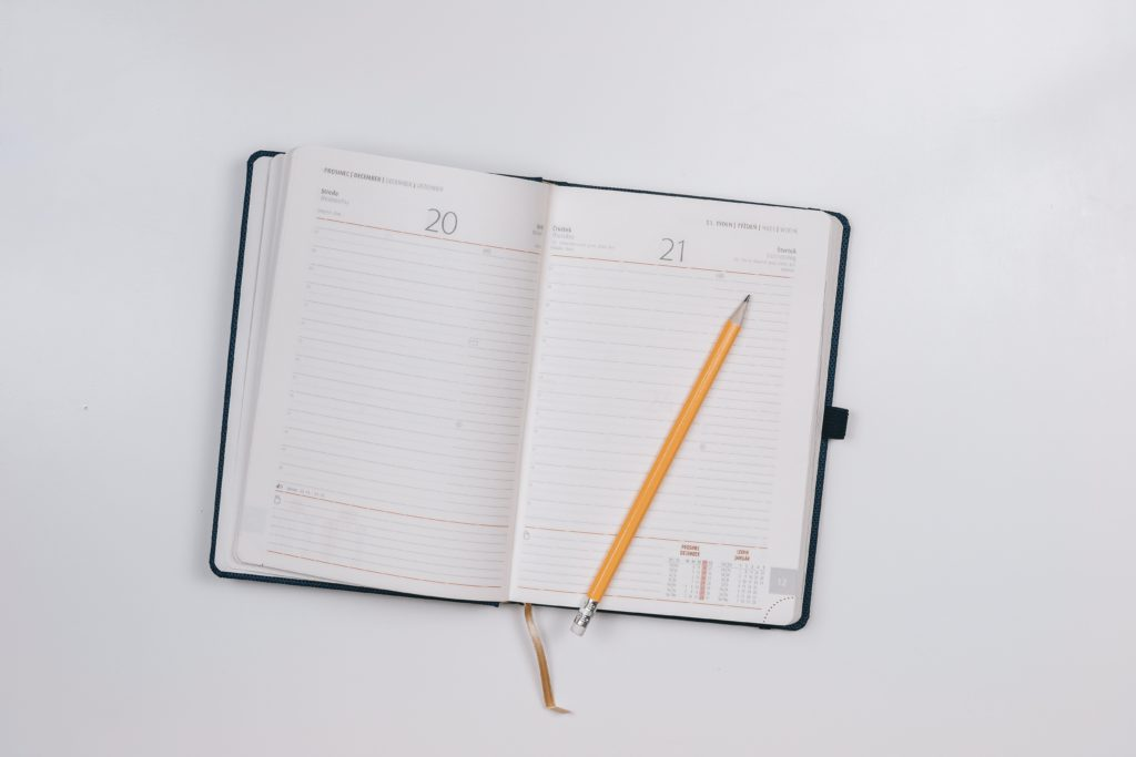 Open and empty planner with pen laying on top