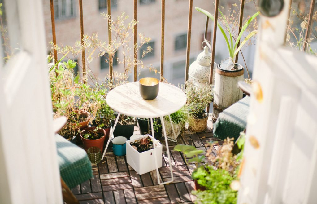 Small balkony with plants, decoration and a little table.