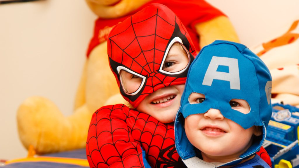 Two little boys, one with spiderman costume, the other one with captain america costume.