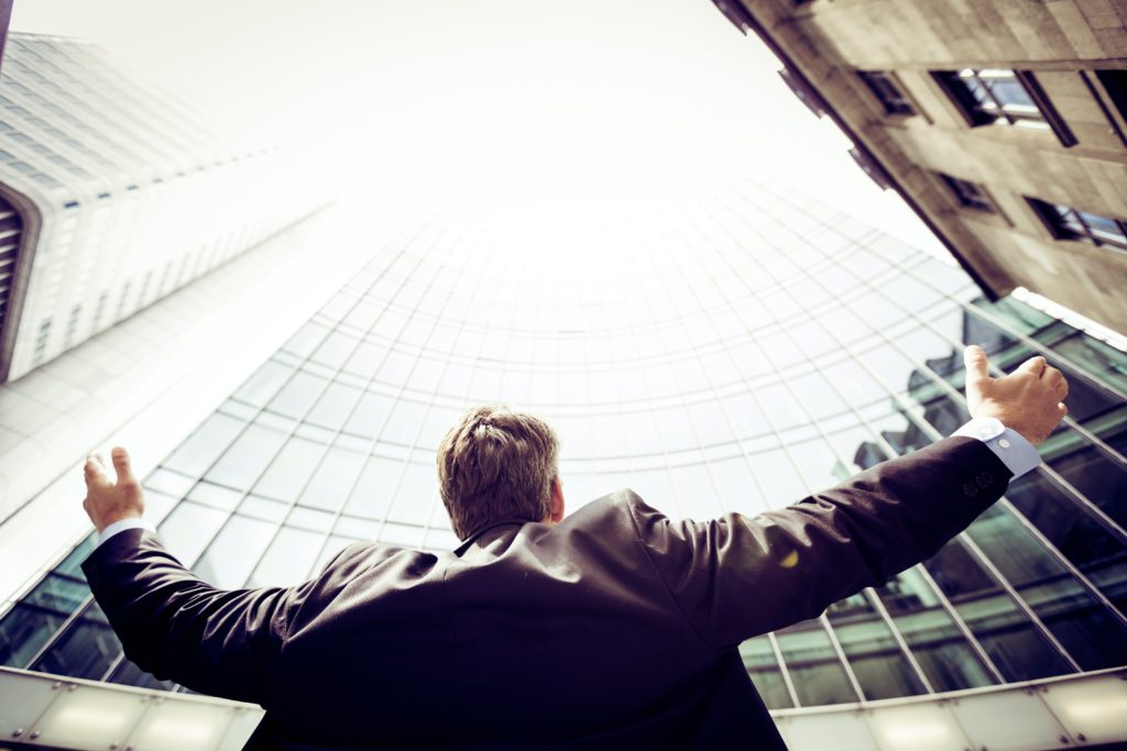 Man celebrating his success by putting his hands in the air in front of a high building